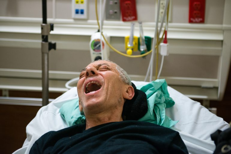 John Fornieri, 80, screams in pain as the doctor puts pressure on his hip. Fornieri, an artist with arthritis and a heart condition, was admitted to the hospital after he lost his balance and fell to the ground. (Heidi de Marco/KHN)
