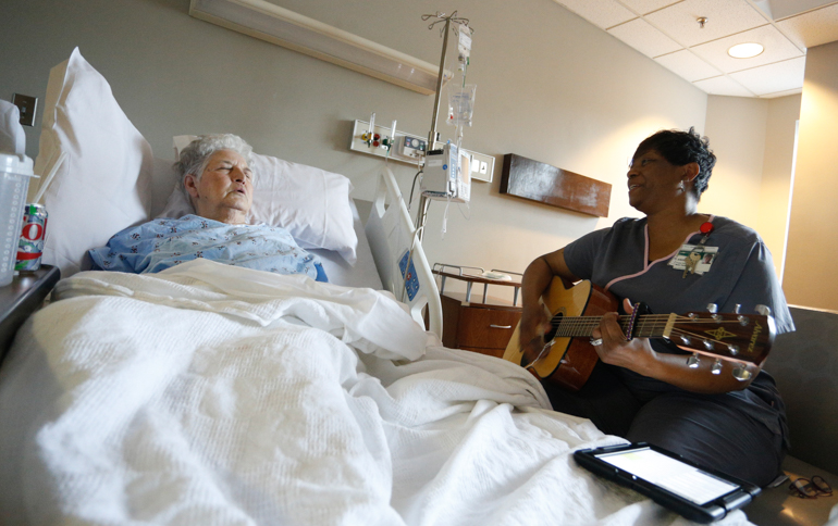 Queze Ferguson, 75, listens to music therapist Angela Howard sing and play the guitar. Ferguson was hospitalized in the geriatric unit of the University of Alabama Hospital, Birmingham. (Hal Yeager for KHN)