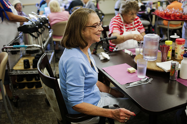 Vivian Malveaux, 81, sits down for a meal at the InnovAge center in Denver. (Nick Cote for The New York Times and Kaiser Health News)
