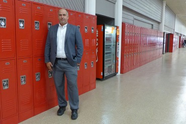Principal John Hurley stands in front of the lockers at High Point Academy in Spartanburg, S.C. (Jenny Gold/KHN)
