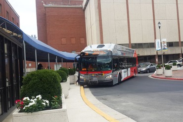 A bus arrives at the bus circle at MedStar Washington Hospital Center in the District of Columbia in July 2016. The hospital is served by many buses, vans and shuttles that come through the circle frequently. (Zhai Yun Tan/KHN)