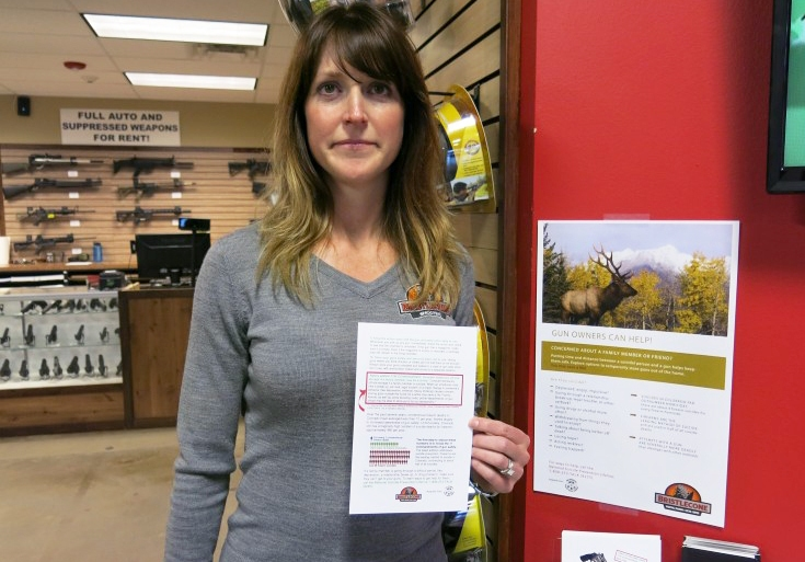 "Jacquelyn Clark, co-owner of Bristlecone Shooting, Training and Retail Center in Lakewood, Colo., holds a list of gun safety rules. One recommendation: Consider ""off-site storage if a family member may be suicidal."" (John Daley/Colorado Public Radio)"