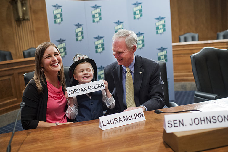 "UNITED STATES - MAY 10: From left, Laura McLinn, of Indianapolis, her son Jordan, 7, and Sen. Ron Johnson, R-Wis., pose for a picture after a news conference in Dirksen Building, May 10, 2016, on the ""Right to Try"" legislation which would allow terminally ill patients, doctors, and pharmaceutical manufacturers to administer investigational treatments when other methods have been exhausted. Jordan suffers from Duchenne muscular dystrophy and his life expectancy is about 20-years-old. (Photo By Tom Williams/CQ Roll Call)"