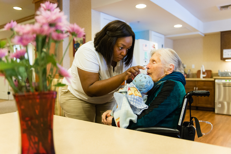 Resident Marilou Roos holds a baby doll while Jessica Butler, a life enrichment manager at Sunrise Senior Living in Beverly Hills, California, helps her take a drink of water on August 2, 2016. (Heidi de Marco/KHN)