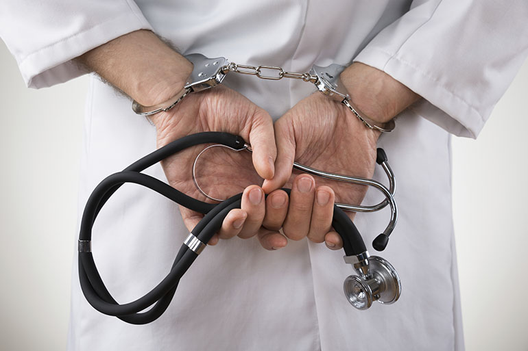 Close-up Of Doctor Hands With Stethoscope In Handcuffs