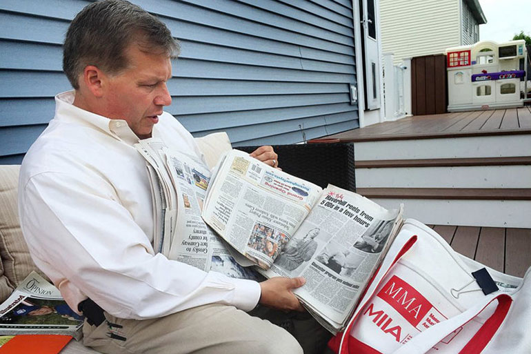 At his home in Haverhill, Mass., Colin LePage leafs through newspapers he shows to middle-schoolers to educate them about the dangers of drugs. (Martha Bebinger/WBUR)