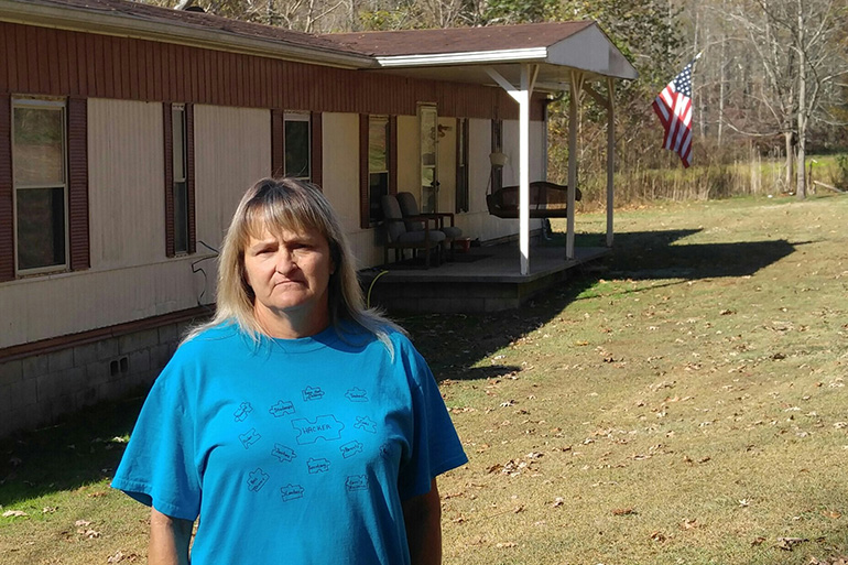 Freida Lockaby of Manchester, Ky., stands outside the mobile home she rents. She says she has benefited from gaining access to Medicaid. (Phil Galewitz/KHN)
