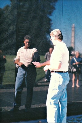 """Photo of Jim at the wall in 1999 or 2000, touching the name of a man who died the same day Jim was injured. """"My name should be there instead of his,"""" he said. (Courtesy of the McGough family)"""