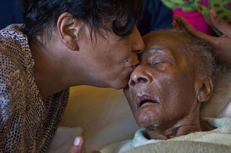 Bobo gives her mother a kiss. Her mother can't talk or move her arms or legs. (Kimberly Paynter/WHYY)
