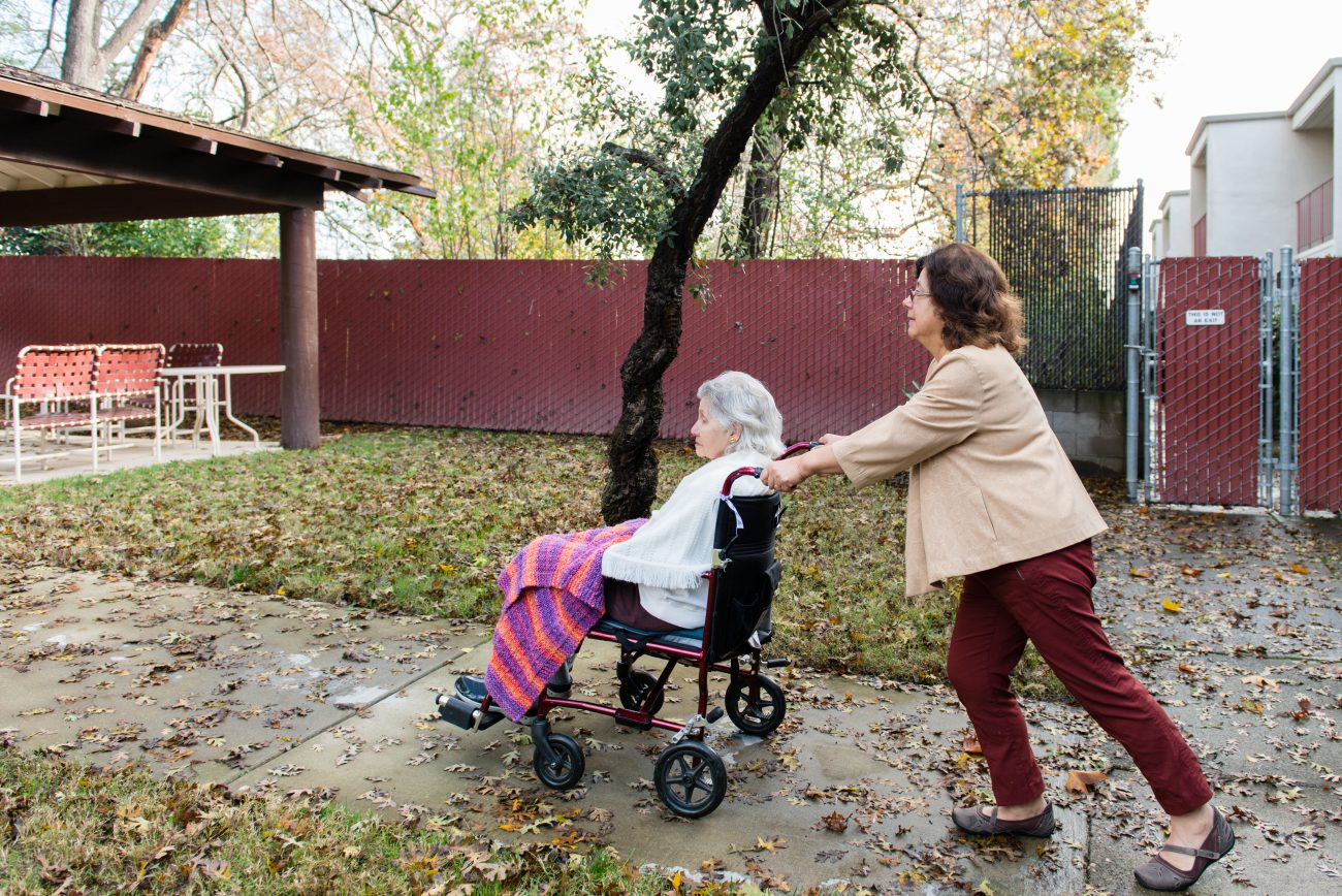 Barbara Marquez takes her mother, Florence Marquez, on a walk on Friday, December 16, 2016. (Heidi de Marco/KHN)
