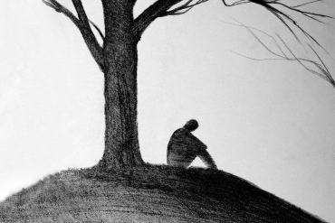 man sitting under tree