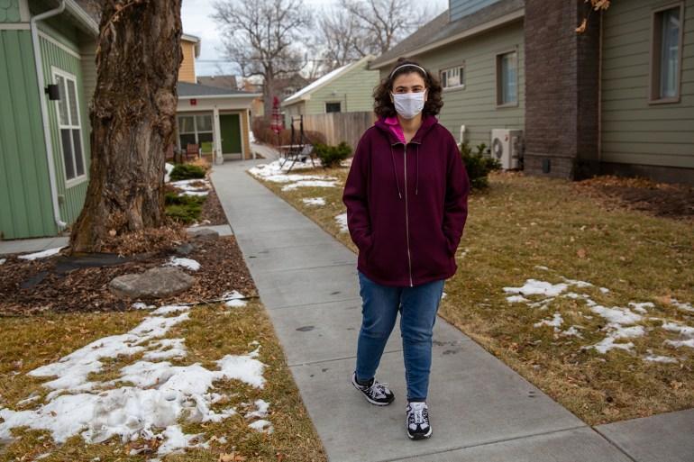 Suzan Mubarak stands outside, wearing a face mask