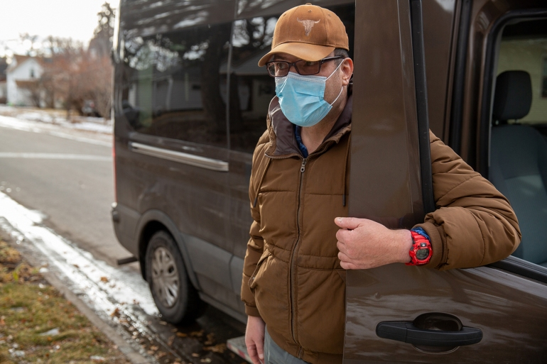 Mitch Domier stands outside beside a van, wearing a face mask