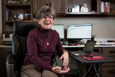 Photo of Marilyn Bartlett sitting at her desk smiling