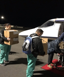 a team of five people carry boxes of vaccines