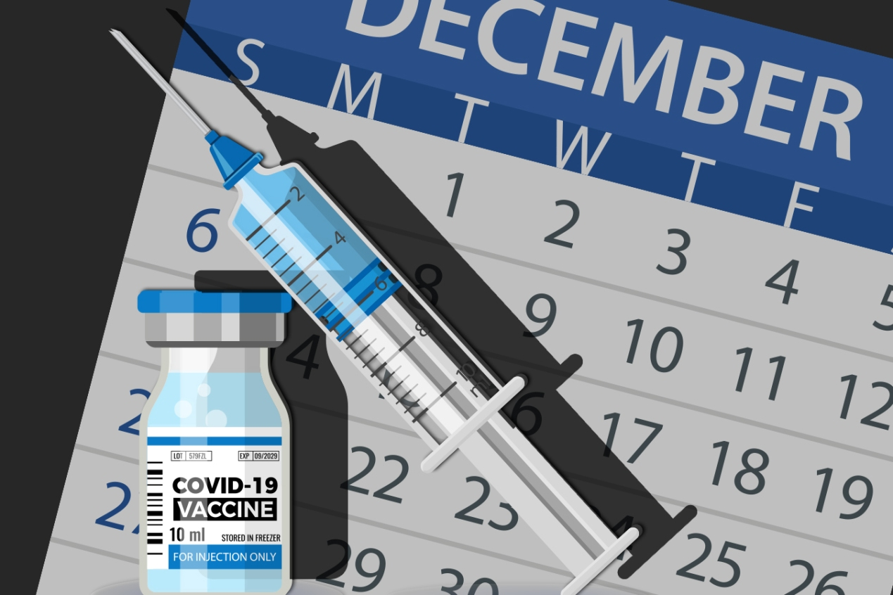 Syringe of covid-19 vaccine in front of a December 2020 calendar
