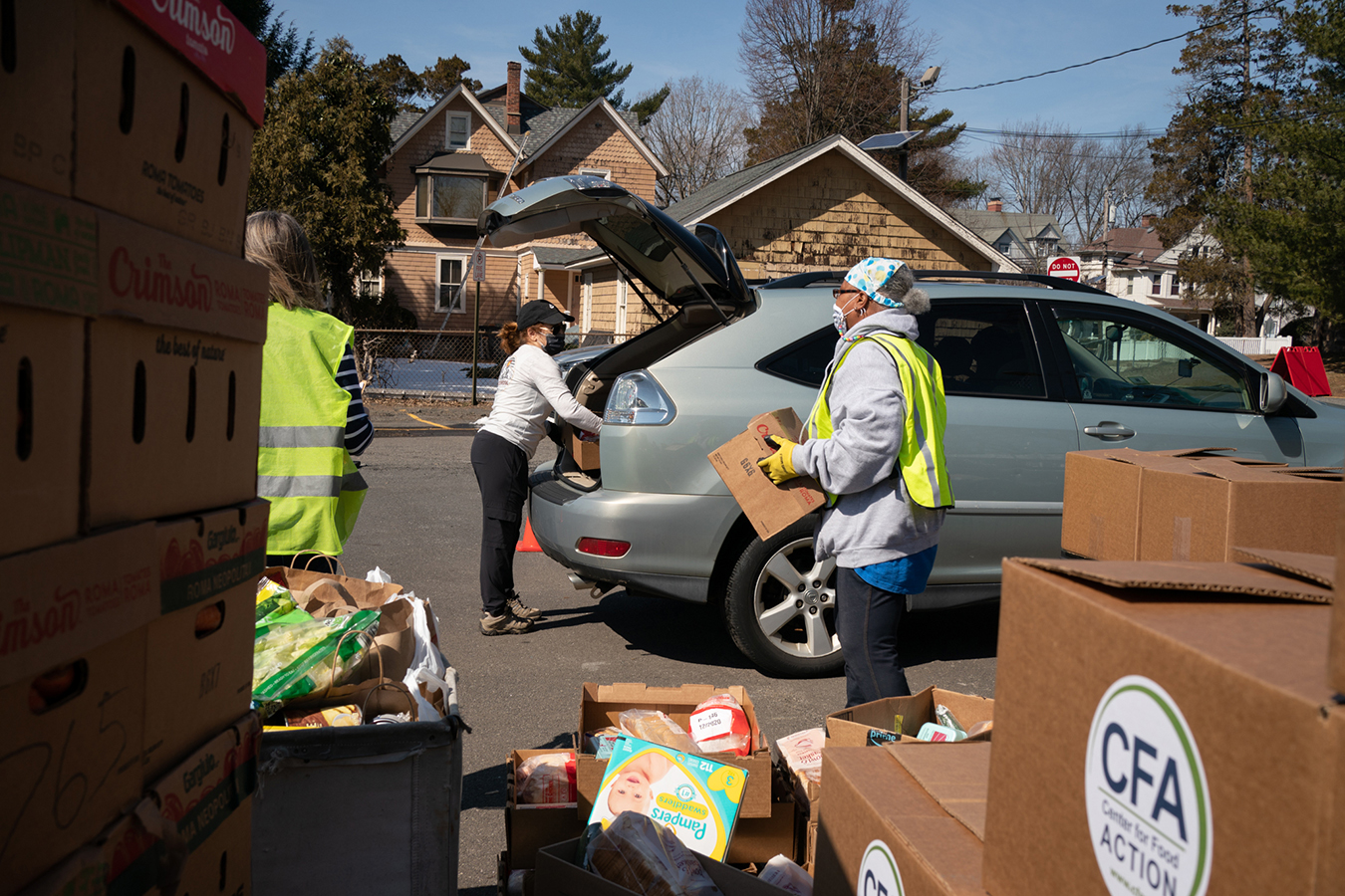 Food pantry volunteers load food into cars