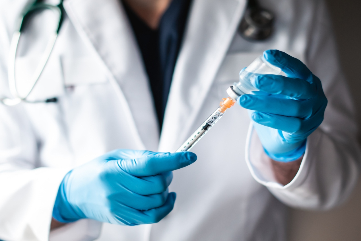 Doctor in white coat drawing vaccine into a syringe for injection.