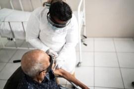 A health worker vaccinates a senior man