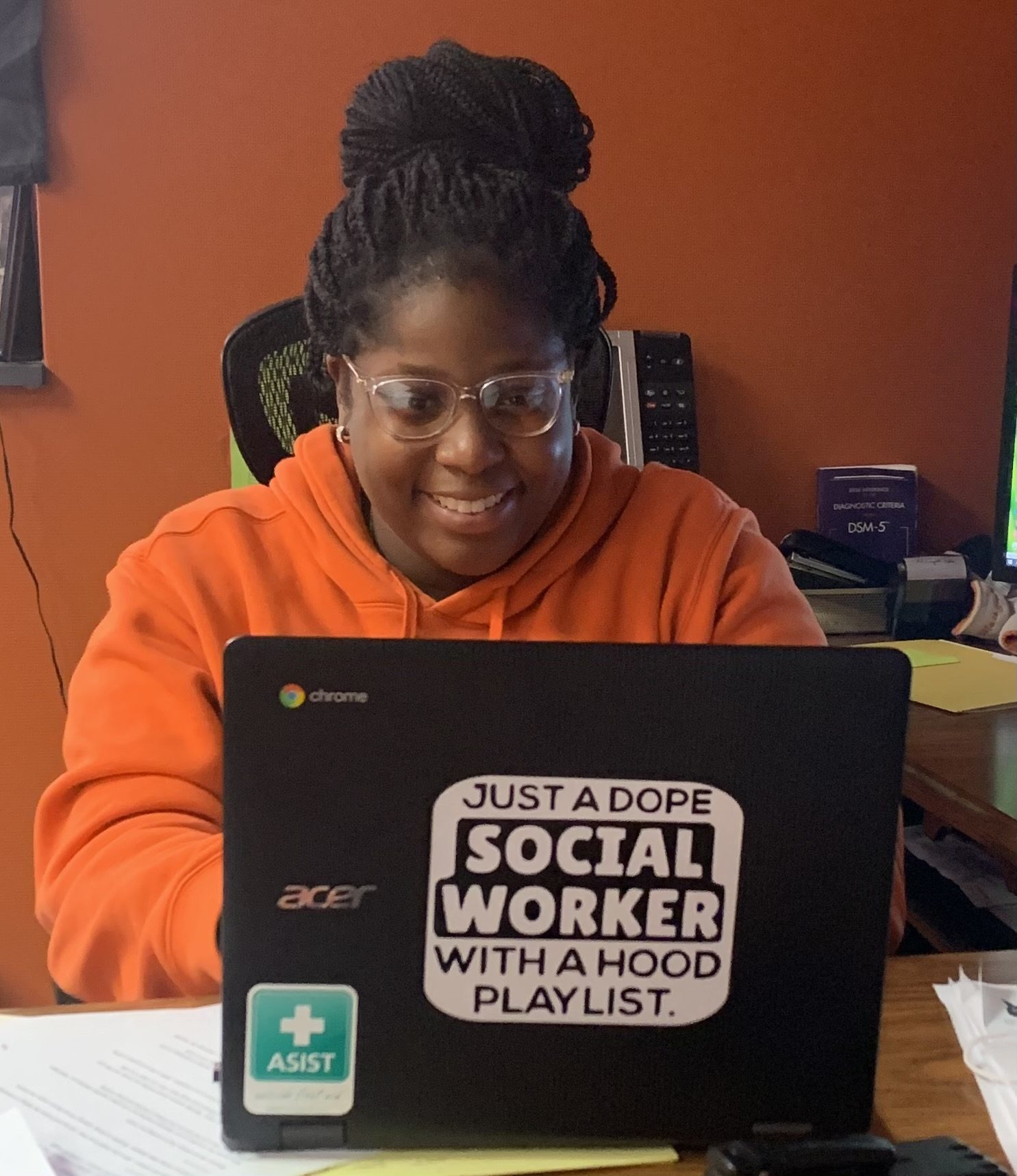 زنی که جلوی لپ تاپ نشسته و لبخند می زند