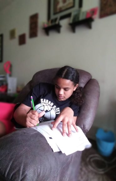 young girl writing while seated on couch with papers on the armrest and a pen in hand