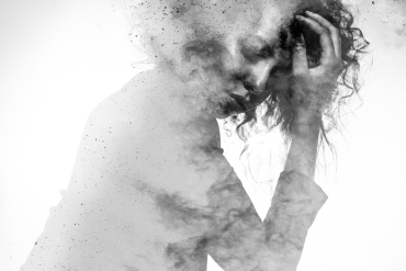 Unhappy woman's form double exposed with paint splatter effect