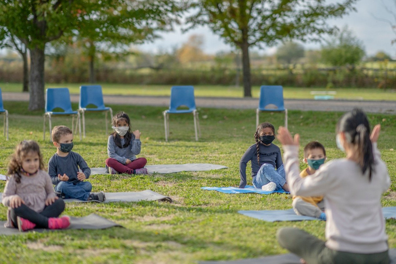 Diverse group of students sitting outside on yoga mats while wearing protective face masks during the COVID-19 pandemic.