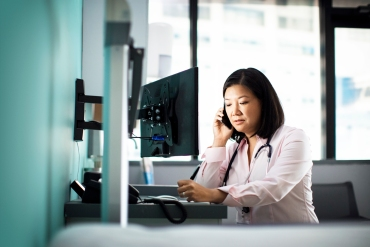 Female doctor using smart phone computer desk in clinic