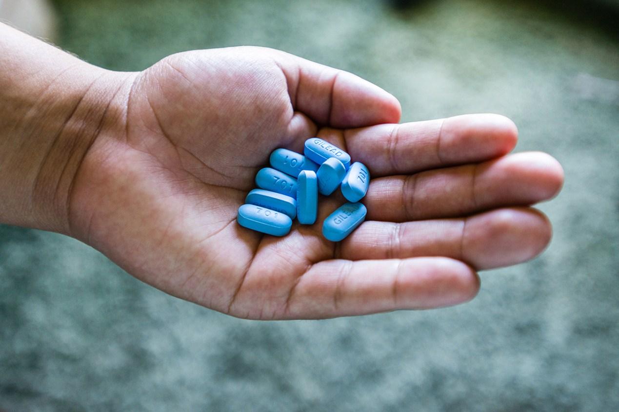 A hand holding blue Truvada pills