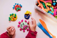 Child playing with plasticine at home making virus